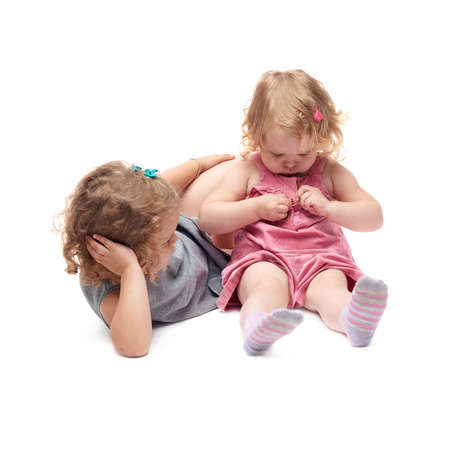 questioned: Couple of young little girls sisters with curly hair in gray and pink dress sitting over isolated white background Stock Photo