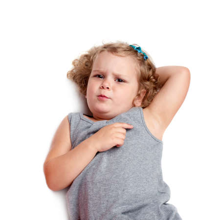 questioned: Young little girl with curly hair in gray dress lying over isolated white background Stock Photo