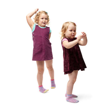questioned: Couple of young little girls sisters with curly hair in purple dress standing over isolated white background Stock Photo