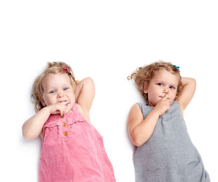 shh: Couple of young little girls sinsters with in gray and pink dress lying and doing shh silence sign over isolated white background