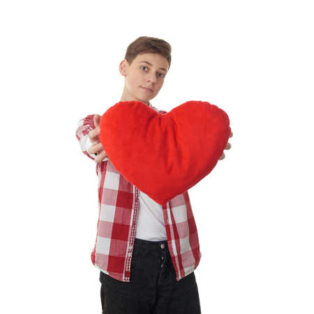 teen love: Cute teenager boy in red checkered shirt with plush heart over white isolated background, half body