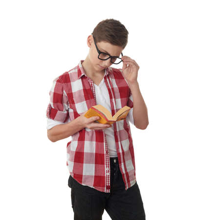 poor eyesight: Cute teenager boy in red checkered shirt, glasses and a book over white isolated background, half body, reading concept