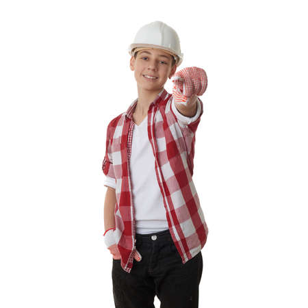 constructing: Cute teenager boy in red checkered shirt and building helmet pointing forward over white isolated background, half body, constructing concept