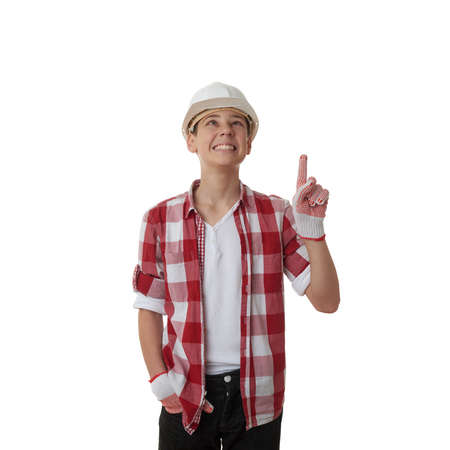constructing: Cute teenager boy in red checkered shirt and building helmet pointing up over white isolated background, half body, constructing concept