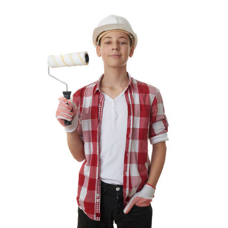 red paint roller: Cute teenager boy in red checkered shirt, building helmet and paint roller over white isolated background, half body, constructing concept Stock Photo