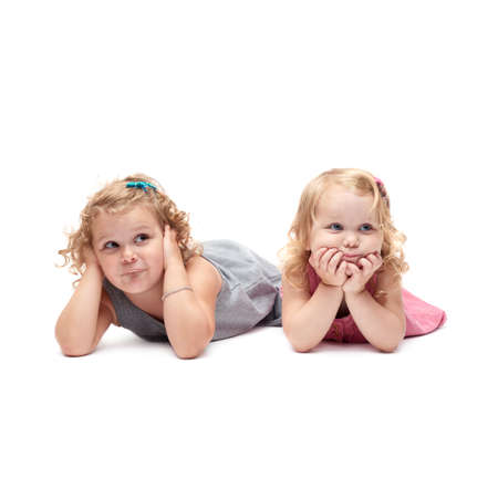 questioned: Couple of young little girls sinsters with curly hair in gray and pink dress lying over isolated white background