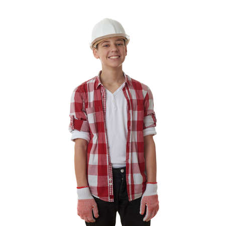 constructing: Cute teenager boy in red checkered shirt and building helmet over white isolated background, half body, constructing concept Stock Photo