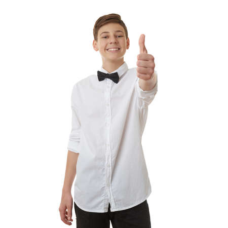 posing  agree: Cute teenager boy in white shirt and black bow tie showing thumb up sign over white isolated background, half body