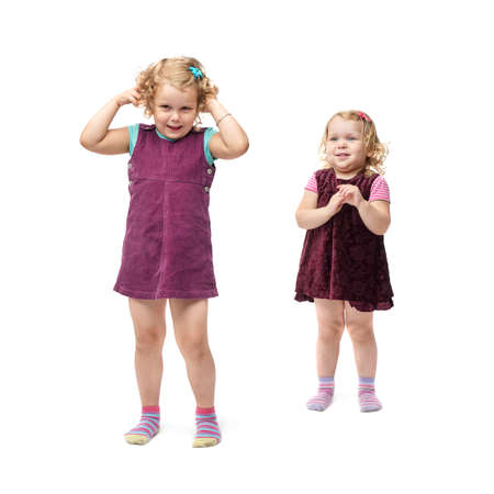 indignant: Couple of young little girls sisters with curly hair in purple dress standing over isolated white background Stock Photo