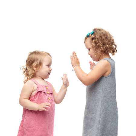 games hand: Couple of young little girls sisters with curly hair in gray and pink dress standing over isolated white background Stock Photo