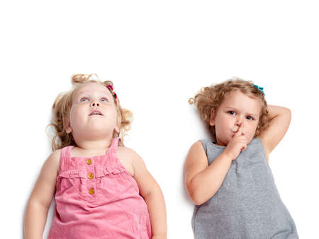questioned: Couple of young little girls sinsters with in gray and pink dress lying and doing shh silence sign over isolated white background