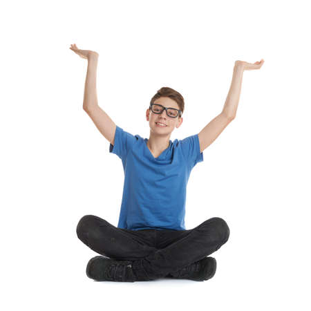 poor eyesight: Cute teenager boy stretching hands up  in blue T-shirt, glasses and lotus posture over white isolated background Stock Photo