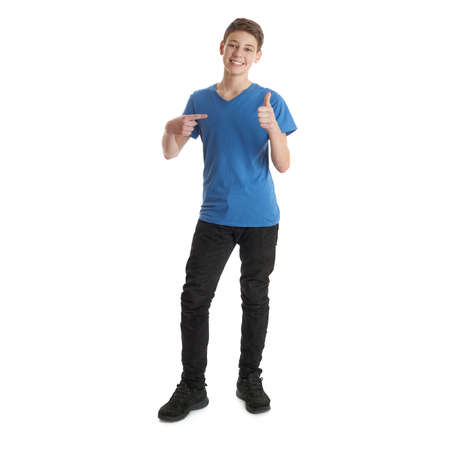posing  agree: Cute teenager boy in blue T-shirt standing and pointing himself over white isolated background full body