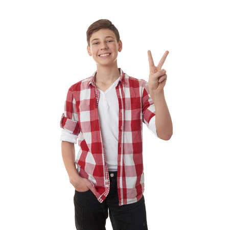 half body: Cute teenager boy in red checkered shirt showing victory sign over white isolated background, half body Stock Photo