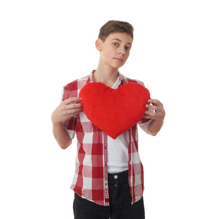 half body: Cute teenager boy in red checkered shirt with plush heart over white isolated background, half body