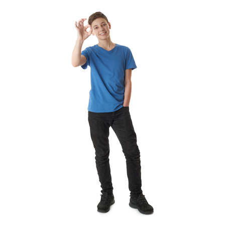 Cute teenager boy in blue T-shirt standing and showing OK sign over white isolated background full body