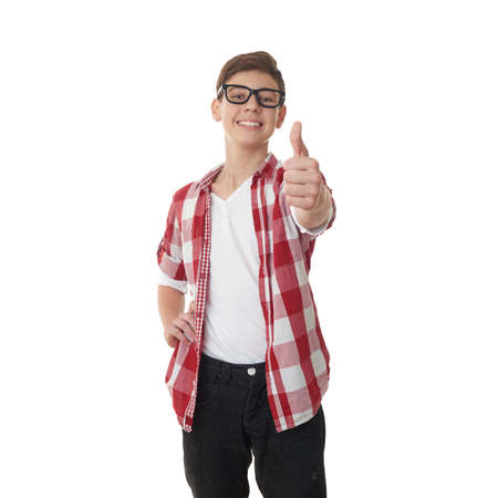 Cute teenager boy in red checkered shirt and glasses showing thumb up sign over white isolated background, half body Stock Photo