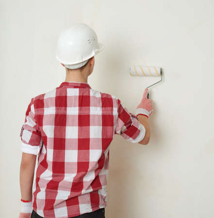 Cute teenager boy in red checkered shirt, building helmet and paint roller against unpainted wall, half body, constructing concept