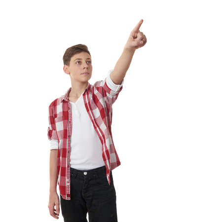 half body: Cute teenager boy in red checkered shirt pointing up side over white isolated background, half body Stock Photo