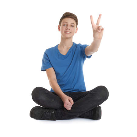 posing  agree: Cute teenager boy showing victory sign in blue T-shirt and lotus posture over white isolated background