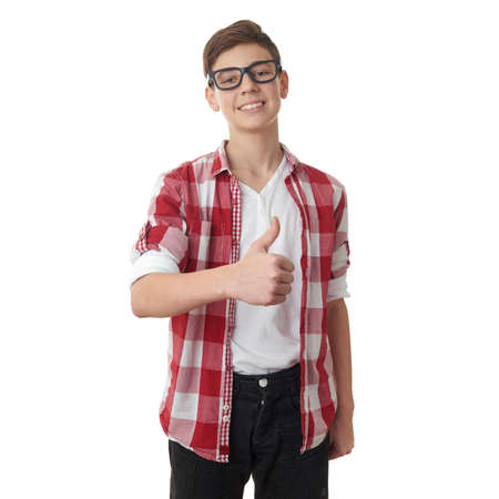 posing  agree: Cute teenager boy in red checkered shirt and glasses showing thumb up sign over white isolated background, half body Stock Photo