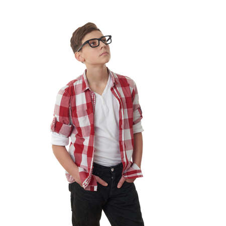 poor eyesight: Cute teenager boy in red checkered shirt and glasses looking side over white isolated background, half body Stock Photo