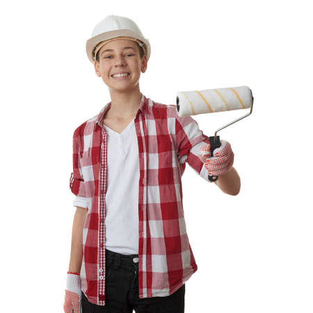 constructing: Cute teenager boy in red checkered shirt, building helmet and paint roller over white isolated background, half body, constructing concept Stock Photo