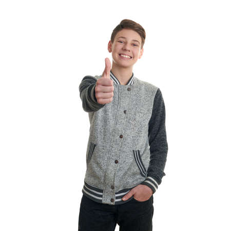 posing  agree: Cute teenager boy in gray sweater showing thumb up sing over white isolated background, half body