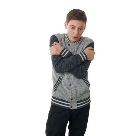 half body: Cute teenager boy in gray sweater trying get warmer over white isolated background, half body