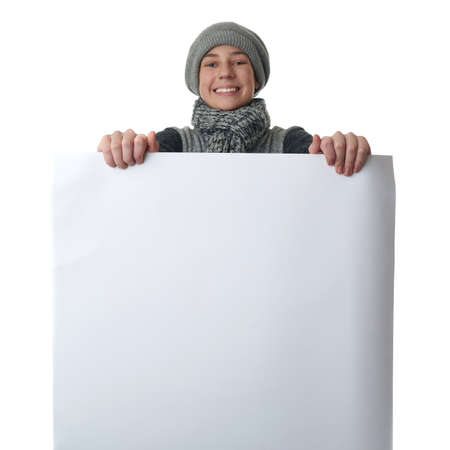 bill board: Cute teenager boy in gray sweater, hat and scarf holding paper bill board over white isolated background, half body Stock Photo