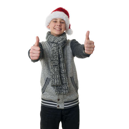 posing  agree: Cute teenager boy in gray sweater and christmas hat showing thumb up sign over white isolated background, half body Stock Photo