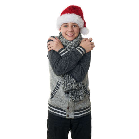 to get warm: Cute teenager boy in gray sweater and christmas hat trying get warm with crossed arms over white isolated background, half body Stock Photo