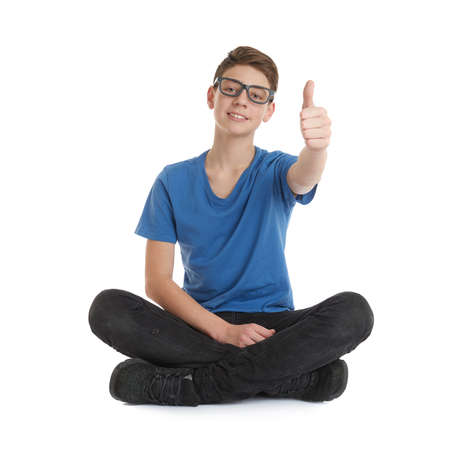poor eyesight: Cute teenager boy in blue T-shirt, glasses and lotus posture over white isolated background