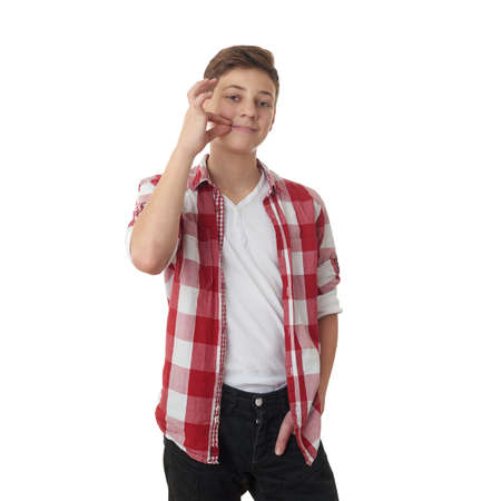 Cute teenager boy in red checkered shirt with locking mouth sign over white isolated background, half body