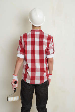 unpainted: Cute teenager boy in red checkered shirt, building helmet and paint roller against unpainted wall, half body, constructing concept