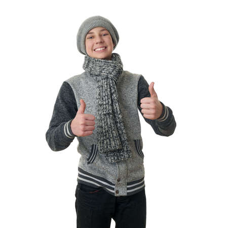 posing  agree: Cute teenager boy in gray sweater, hat and scarf showing thumb up sign over white isolated background, half body