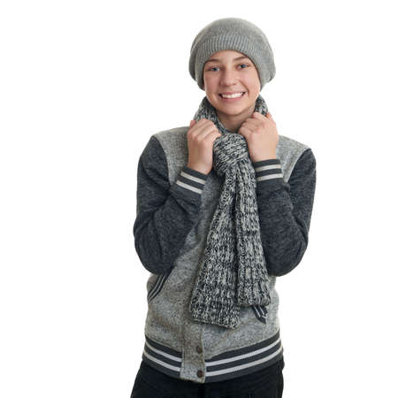 half body: Cute teenager boy in gray sweater, hat and scarf over white isolated background, half body