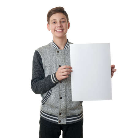 bill board: Cute teenager boy in gray sweater holding paper bill board over white isolated background, half body Stock Photo