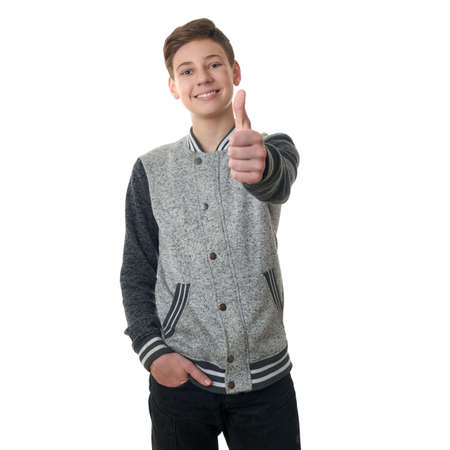 Cute teenager boy in gray sweater showing thumb up sing over white isolated background, half body