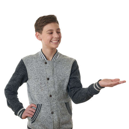 half body: Cute teenager boy in gray sweater presenting something on hand over white isolated background, half body Stock Photo