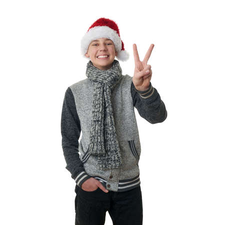 Cute teenager boy in gray sweater and christmas hat showing victory sign over white isolated background, half body