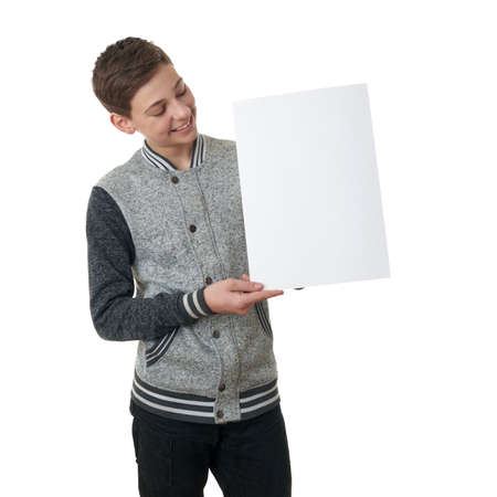 paper sheets: Cute teenager boy in gray sweater holding paper bill board over white isolated background, half body Stock Photo