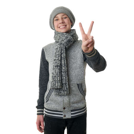 Cute teenager boy in gray sweater, hat and scarf showing victory sign over white isolated background, half body