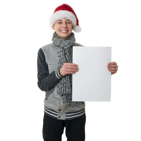 Cute teenager boy in gray sweater and christmas hat holding paper over white isolated background, half body Stock Photo