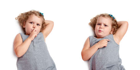 shh: Young little girl with curly hair in gray dress lying and doing shh silence sign over isolated white background Stock Photo