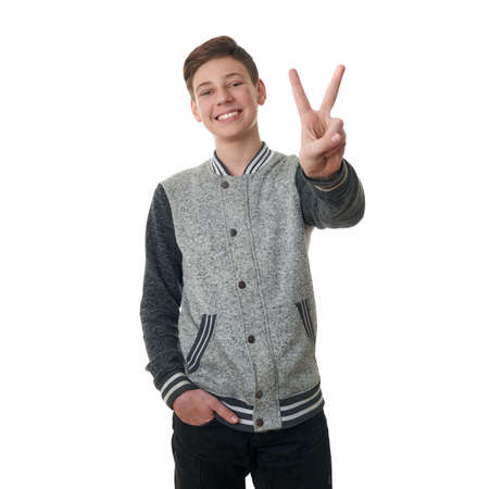 Cute teenager boy in gray sweater showing victory sing over white isolated background, half body