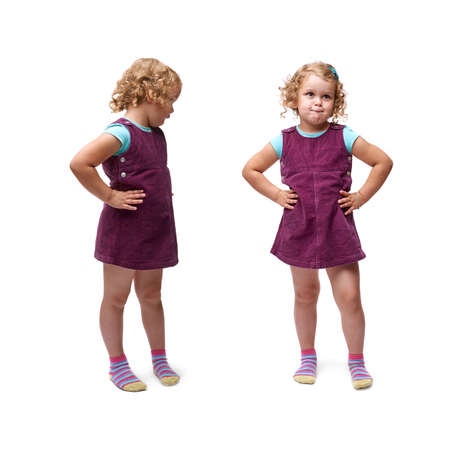 Young bewildered little girl with curly hair and arm on hips in purple dress standing over isolated white background Stock Photo