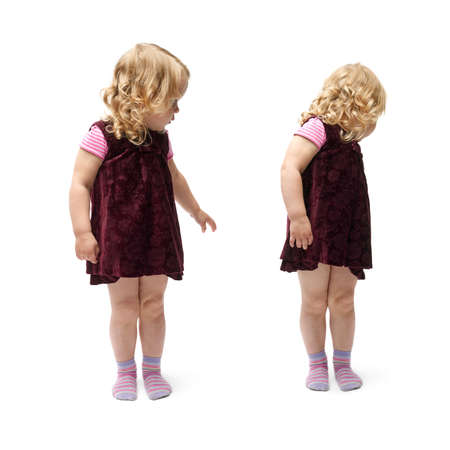 turn away: Young little girl with curly hair in purple dress standing and looking back over isolated white background Stock Photo