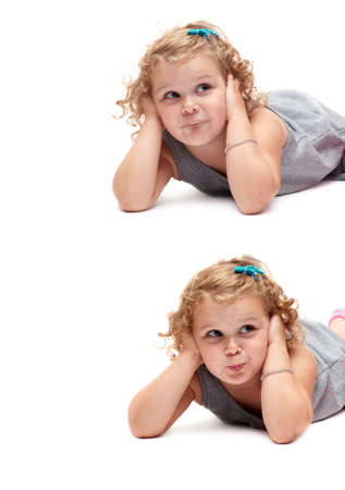 Young little girl with curly hair in gray dress lying over isolated white background Stock Photo
