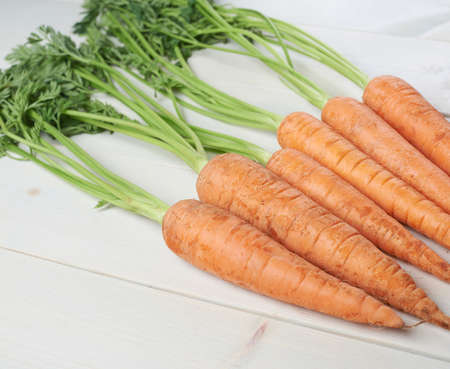Bunch of raw whole carrots on white wooden surface table
